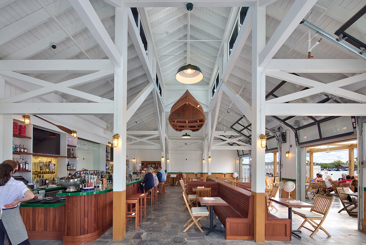The large timber frame interior features a large boat hanging from the rafters.