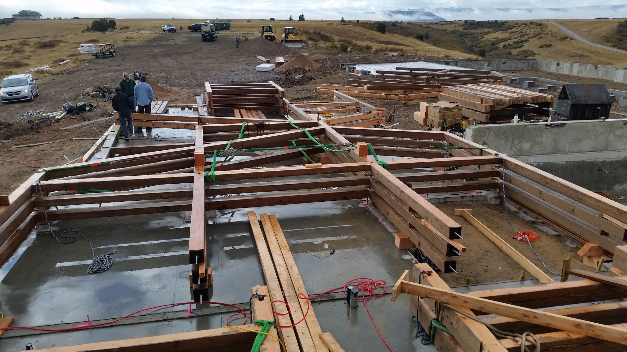 The pre-assembled bents sitting on the barn foundation give a sense of just how large the structure will be once raised.