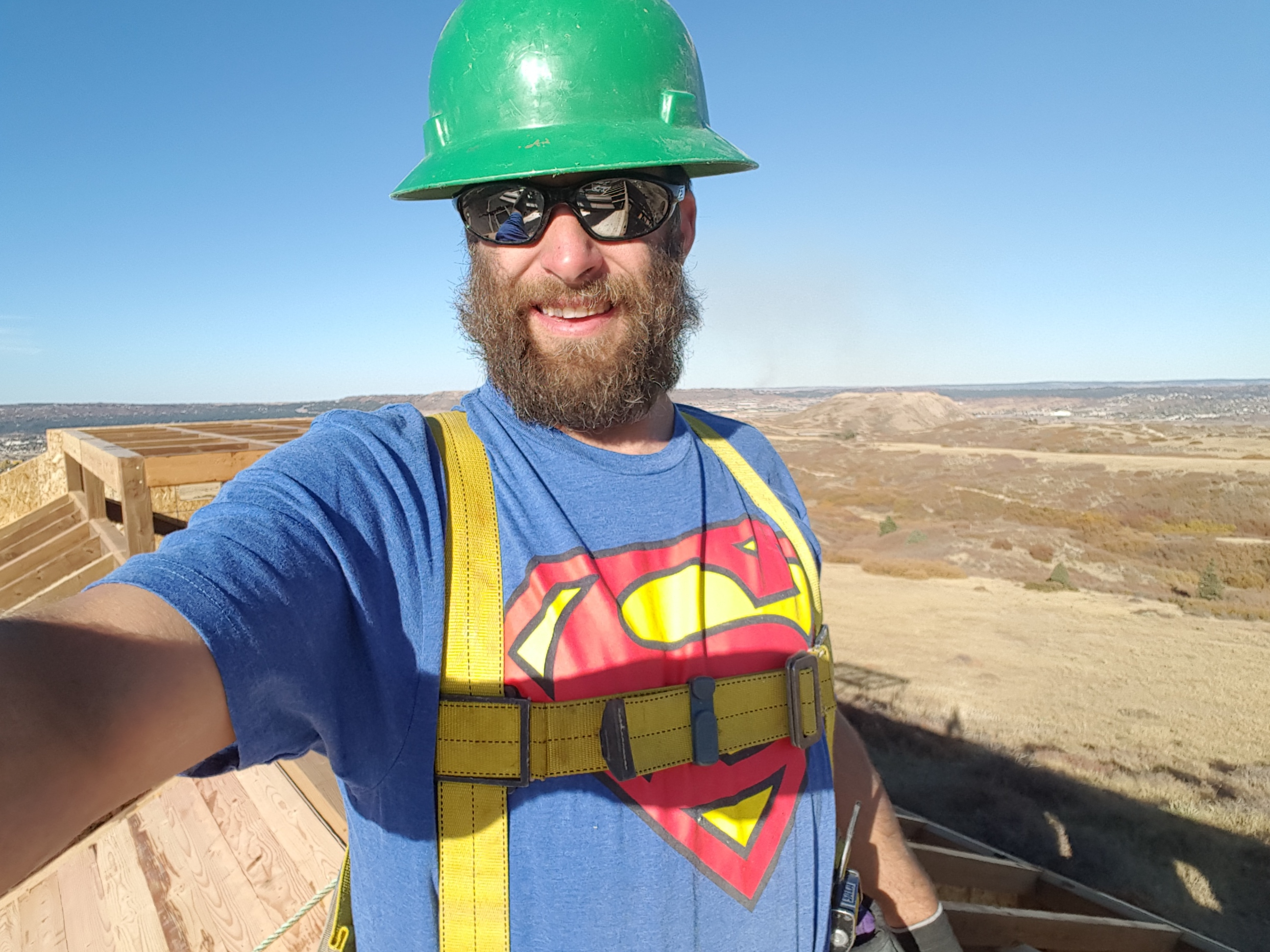 Mike models a Superman t-shirt, a fun gift from a vendor, while installing t&g on the barn roof.