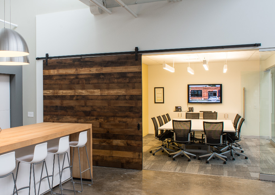 Reclaimed mixed hardwoods were re-worked into a flat track 8'x8′ door for an architecture firm's conference room in Rochester NY. Large flat track doors like this operate more as an easily-moved feature wall. Photo by Scott Hemenway.