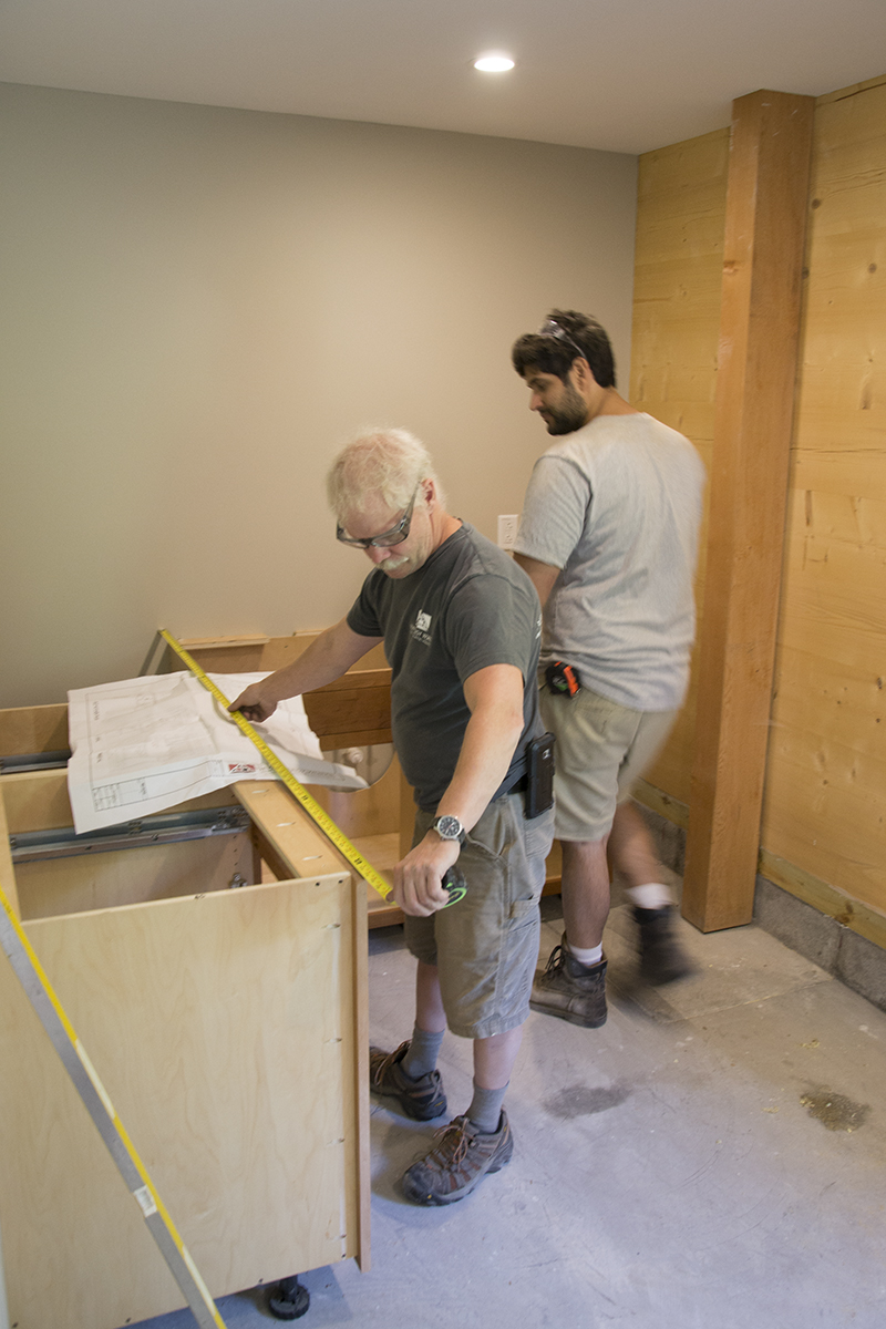 Charlie & Tony work on installing the cabinetry in the break room of the new shop.