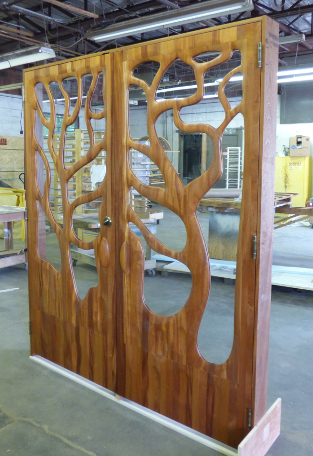 """To create this """"tree door"""", the CNC first hulled out and surfaced the majority of the door. Our door team, lead by Jay, worked the rough output by hand/hand-held machine back to what we see as the final product. As Jay told us, """"Many hands, many touches, many hours. One of the most customized pieces to date."""""""