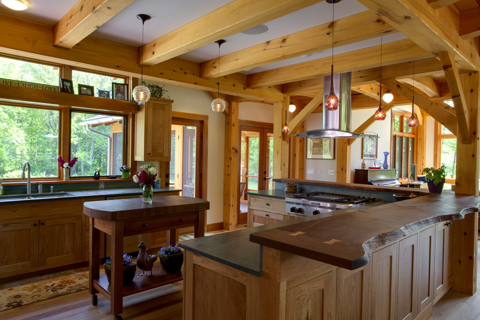 Live edges, butterfly joinery, slate tops, an additional rolling butcher block, and ample counter surfaces afford a growing family space for everyone to participate in kitchen activities.