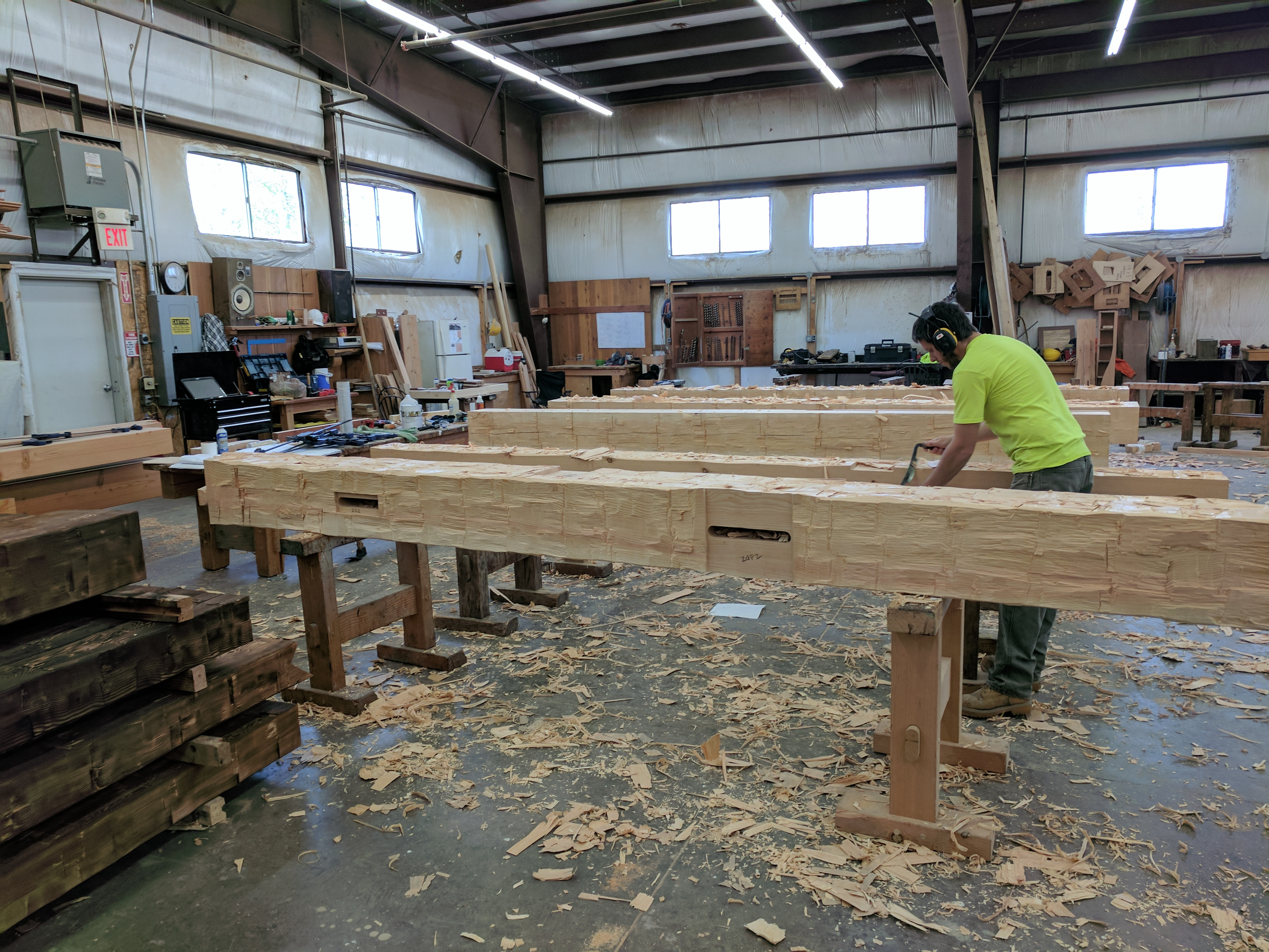 Timber framer Pete adds finishing touches with a draw knife to these hand-hewn timbers.