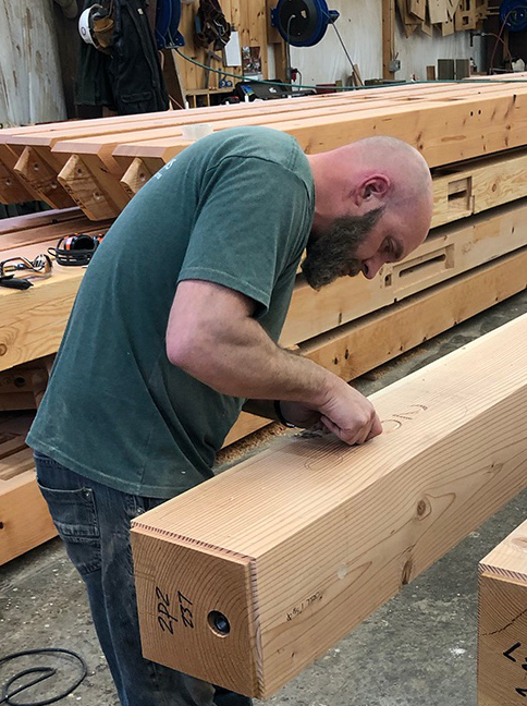 One finishing touch to the LNB timber frame includes a custom carving, commemorating the year the project will be raised, applied by the skilled hands of Jake, one of our long-time craftsmen and project champion.