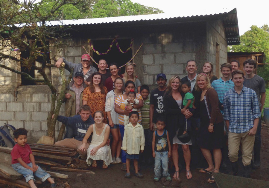 Fifteen volunteers from the Bridges to Community group along with Nicaraguan families gather in front of one of the new homes in El Mojon.