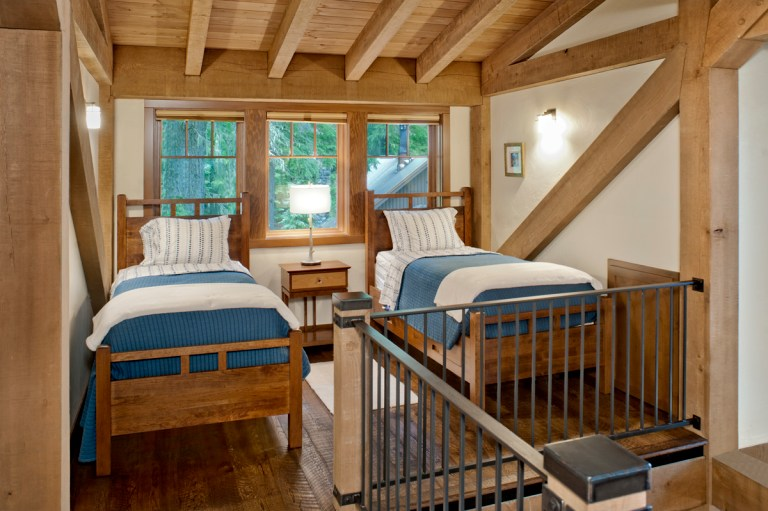 While modest in scale, the upper-level loft offers extra bunk space (above) for family and guests as well as a small gathering space away from the larger common areas (below). Photo (c) Loren Nelson Photography.
