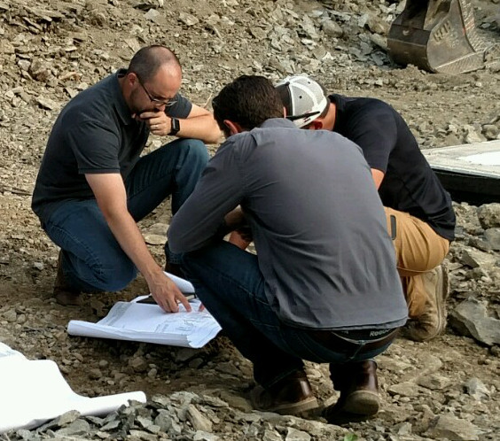 Ty (left) discusses plans on the job site with a few other members of the design/build team.