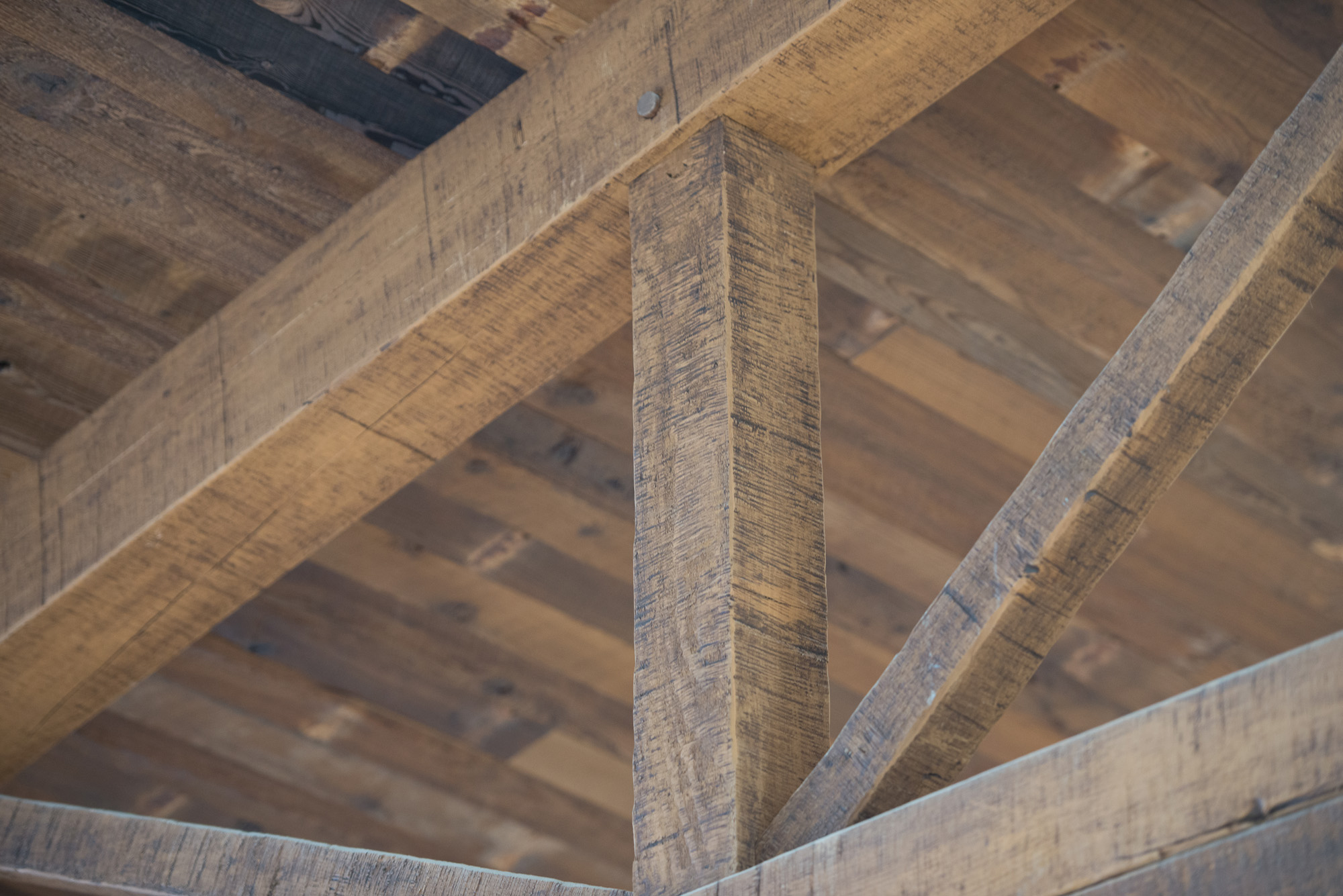 A multi-step finish and additional texture was applied to create a rugged look for the Douglas fir trusses. The t&g ceiling above is reclaimed softwoods.