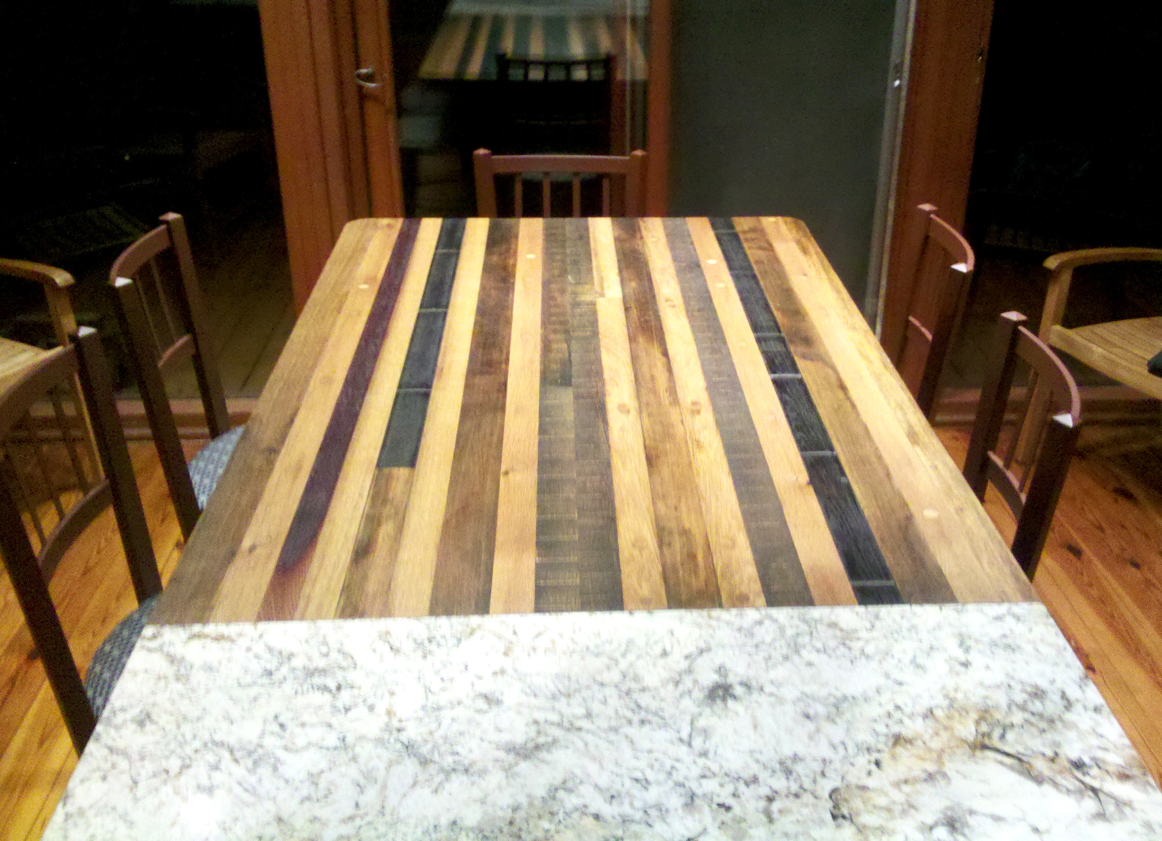 Old French white oak and domestic barrel/vat staves were repurposed into a pier table off the kitchen island, ideally situated for family meals.