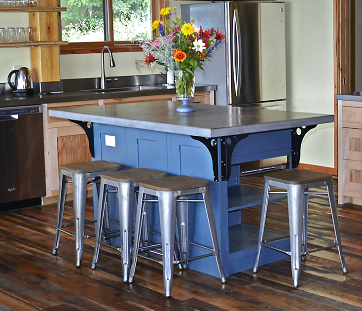 A painted island with a poured top and industrial stools/brackets adds color and functionality to a modest kitchen.