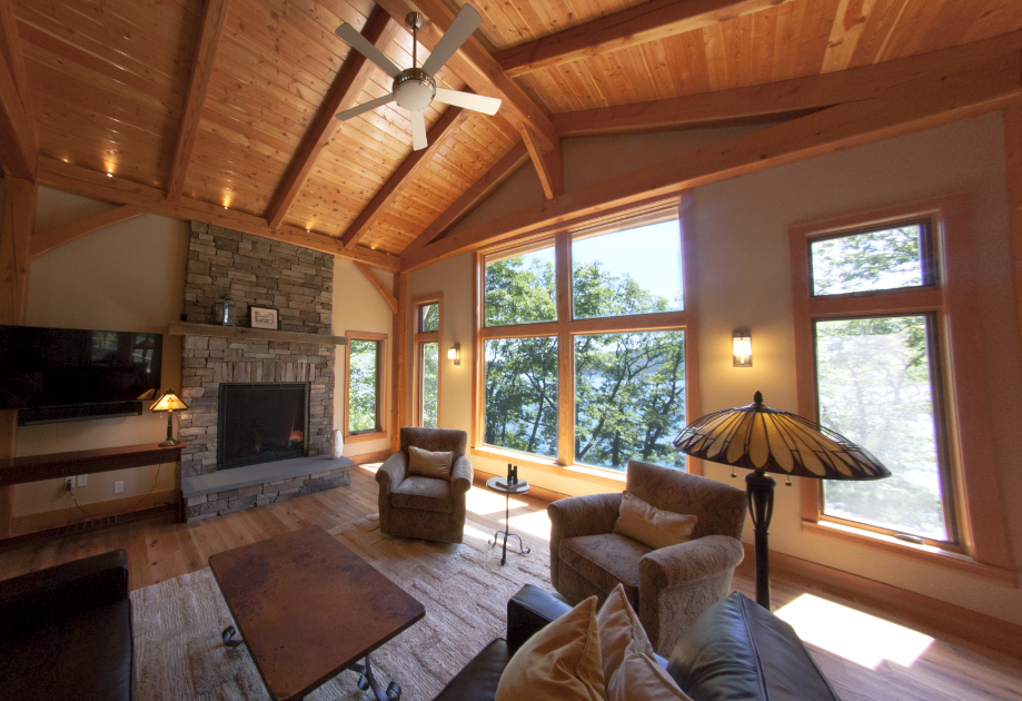 Inside the home, the great room offers intimate volumes while capturing views of the trees and lake outside.