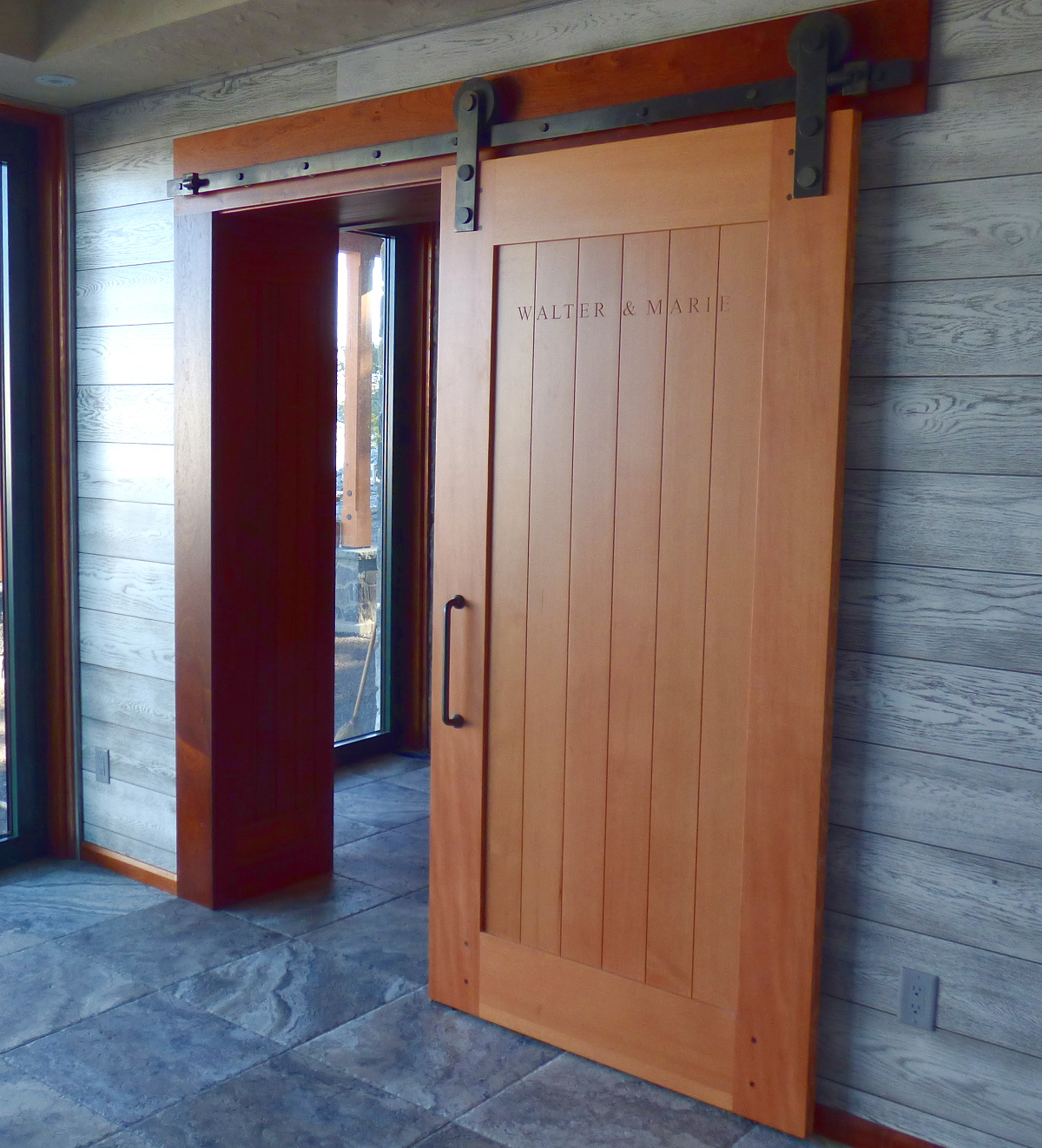 Clean lines and the warm tones of a custom Douglas fir sliding door contrast with the surrounding cool-toned materials.