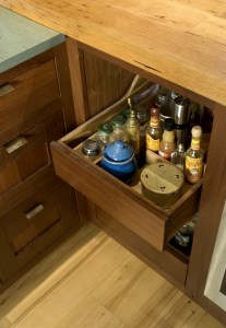 A heavily loaded custom walnut condiment drawer opens weightlessly thanks to TANDEM plus BLUMOTION runner technology.