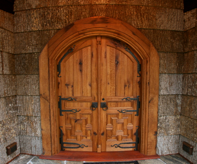 Crafted of reclaimed oak, these custom chapel doors are both arched and curved to match the curving exterior wall.