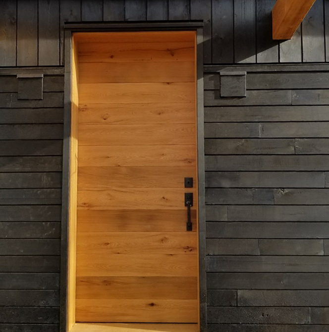 Against traditional shou sugi ban charred siding, a warm-toned reclaimed oak door welcomes all to the Jewel.