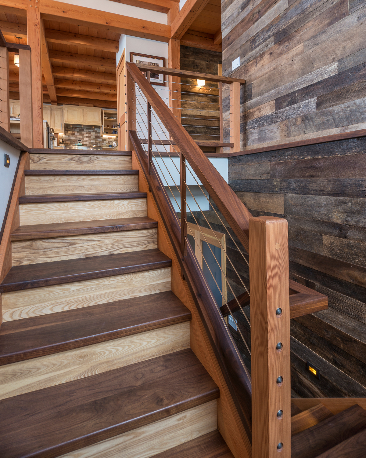 Woods used throughout this Hudson Valley home coalesce in the main stair where the railing/cables mimic the railing found on the outdoor deck (image below). Photo by Scott Hemenway.