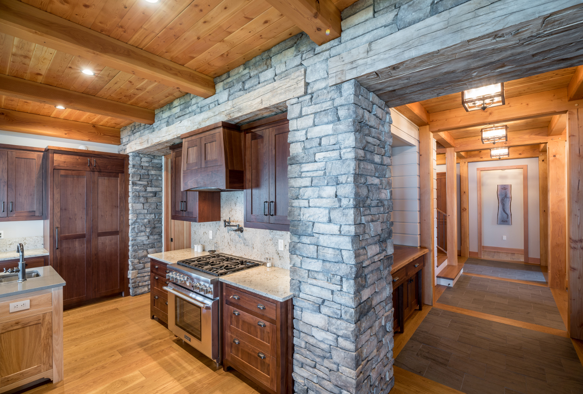 "A substantial 24"" reclaimed timber header within the stone defines the transition from away spaces into the entertainment areas. Photo (c) Scott Hemenway."