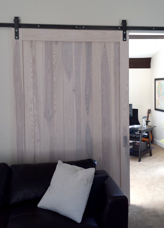 Custom white finish for an interior flat track door aligns with the overall interior decor.