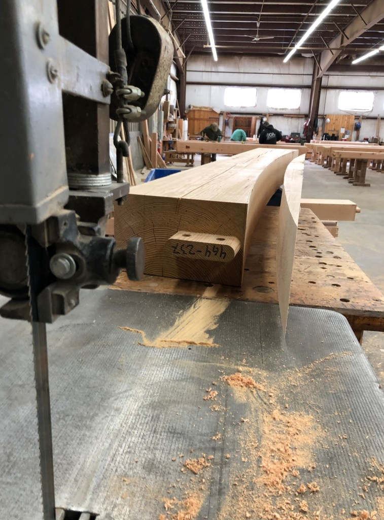 Each bottom cord for the LNB bank frame has a gentle curve cut on the large band saw in our timber frame shop. (10″ is about the biggest timber we'll put through this saw.)