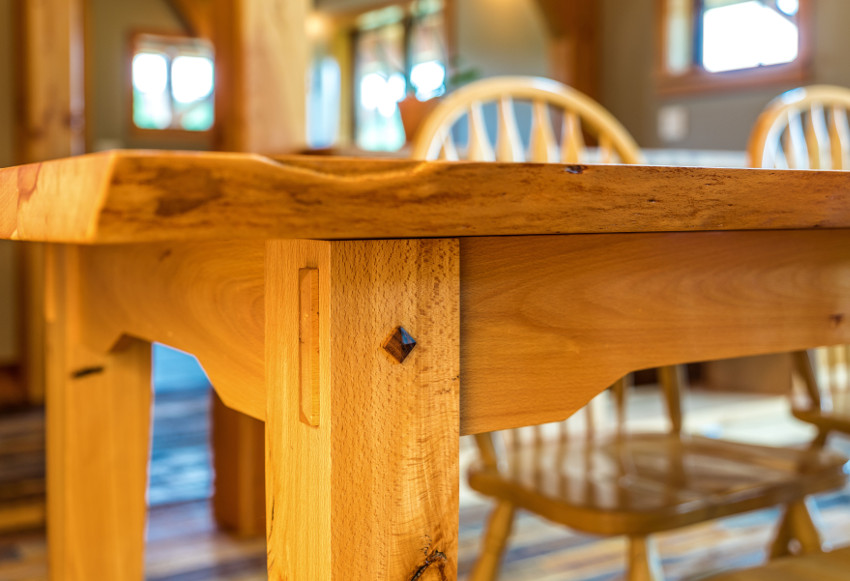 In the details: A reclaimed beech table with live edge, thru-tenon aprons, and walnut pyramid pegs.