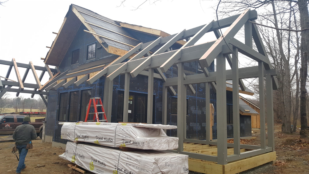 After the high performance enclosure was in place, our timber frame team returned to raise the exterior porch frames and accent pieces, all custom finished to a subtle earth tone.