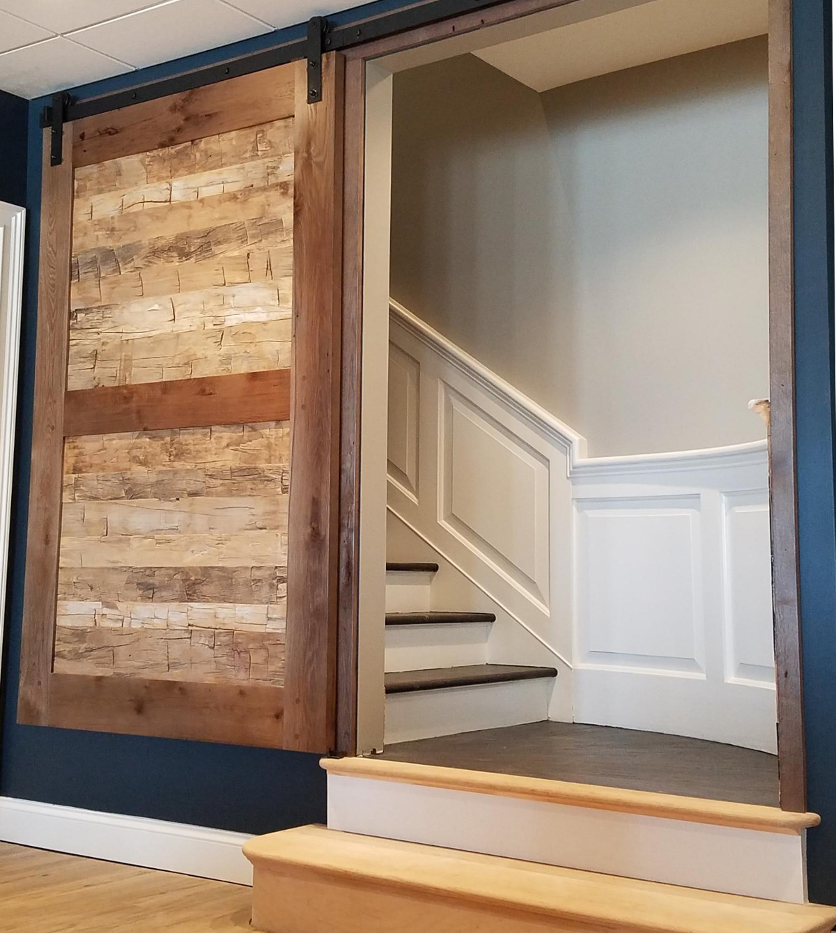 Reclaimed hand hewn timber skins bring texture and character to a lower level rec room entry.