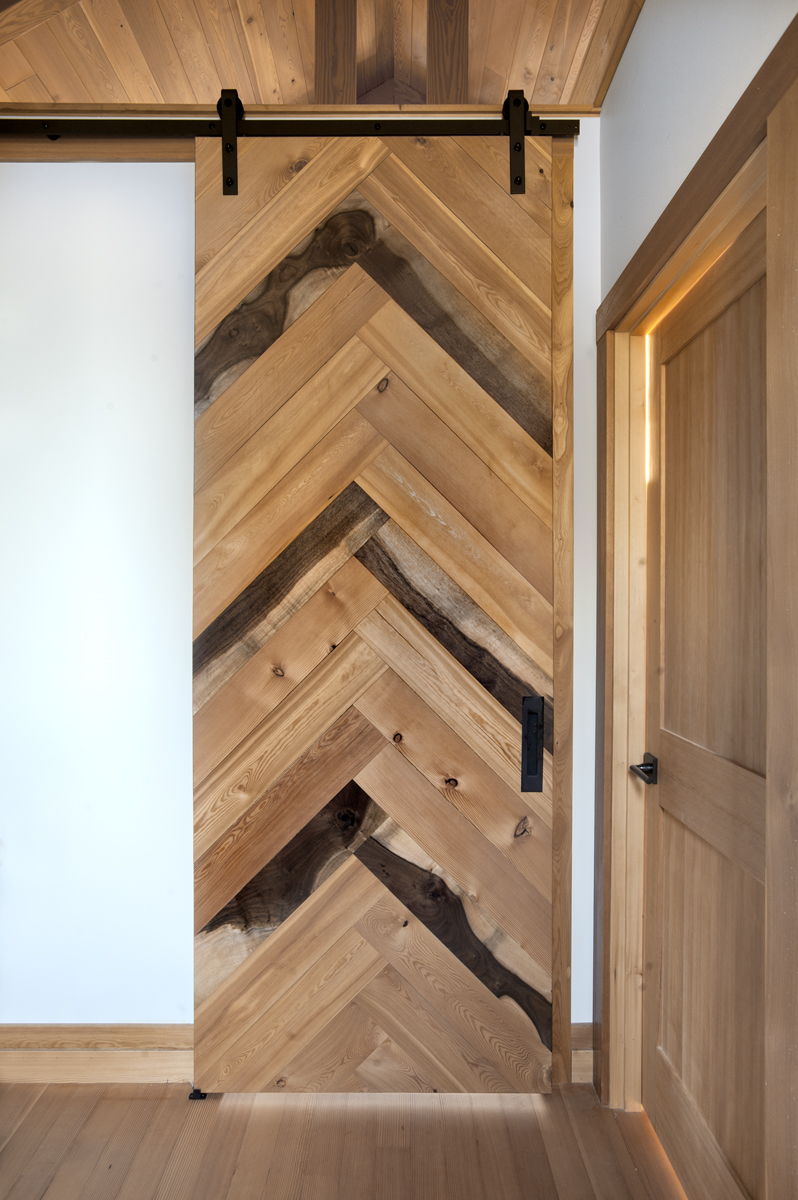 A 'tall' flat track door double faced with a herringbone pattern of Walnut, Larch, and Douglas fir is bedroom and hallway wall art for an Oregon couple's Jewel of a home. Photo by Loren Nelson.