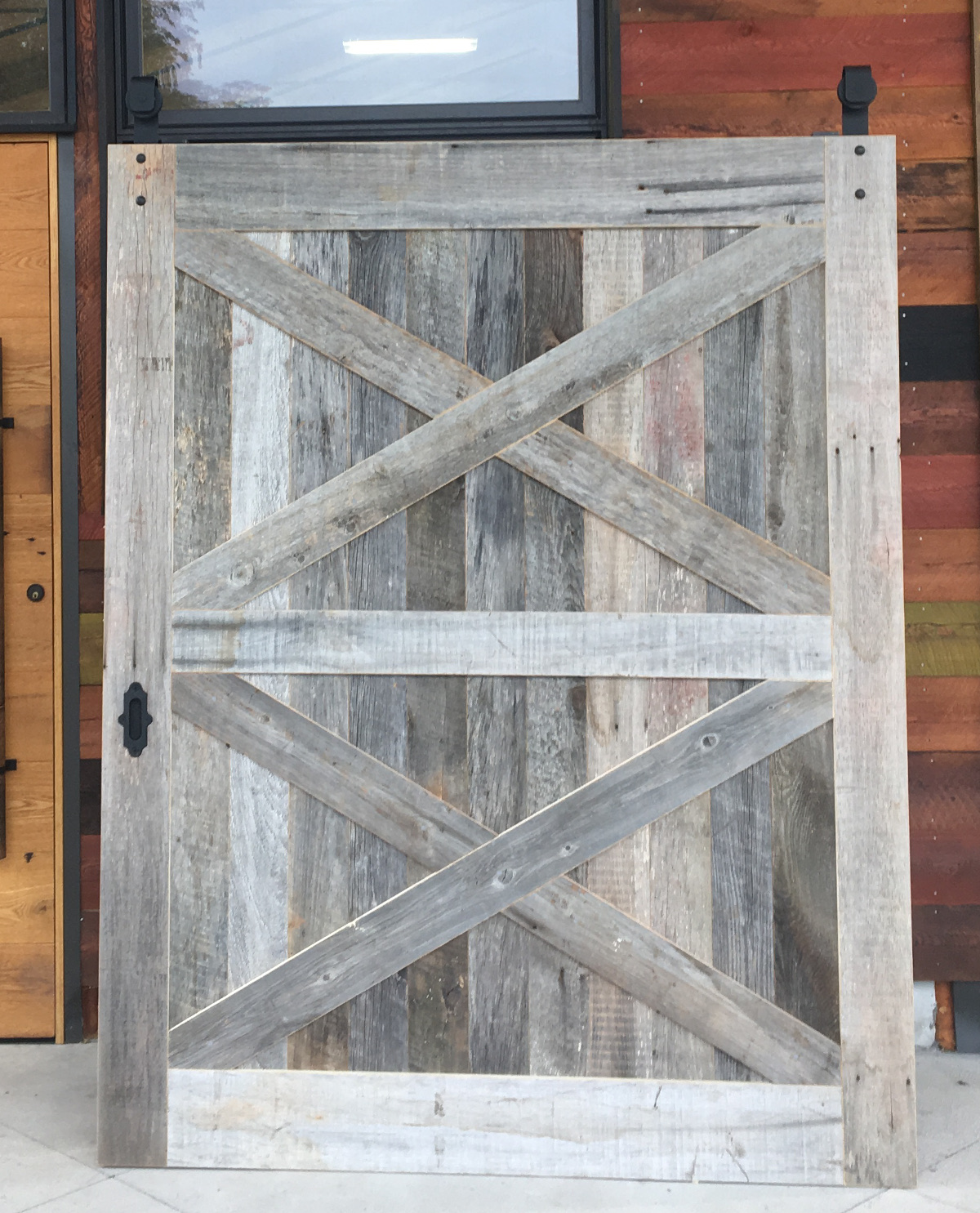A wide double X flat track door crafted of Pioneer Millworks reclaimed American Prairie mixed softwoods.
