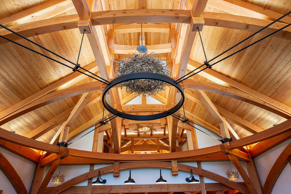 """The resulting 36' x 36' great room is characterized by its """"circle in a square"""" timber frame that is the core to the overall basket-like structure."""