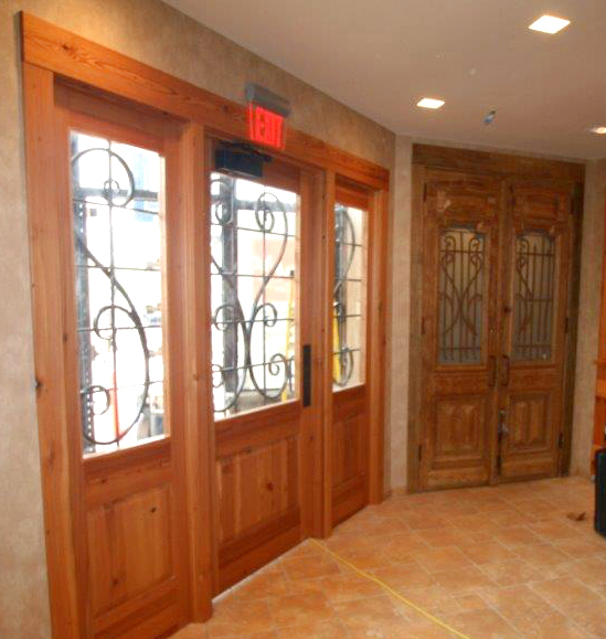 Inspired by the adjacent antique doors, the new main entry door for the eatery entrance was crafted of Reclaimed Heart Pine by NEWwoodworks.
