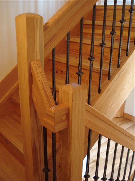 A reclaimed Heart Pine stair with a solid rail including handcrafted returns.