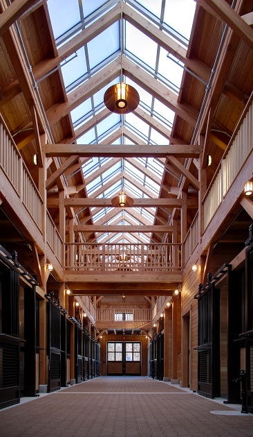 This (amazing!) custom timber frame stable in Massachusetts is nearly ready for equine inhabitants. The open hay loft, clerestory, and large windowed entry doors offer an abundant amount of natural light to the interior spaces. I know my horse would love it here.