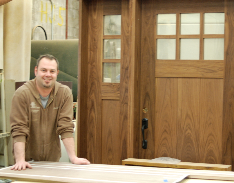Jay Bernard, door guru at NEWwoodworks, pictured with a completed walnut entry door and sidelight.