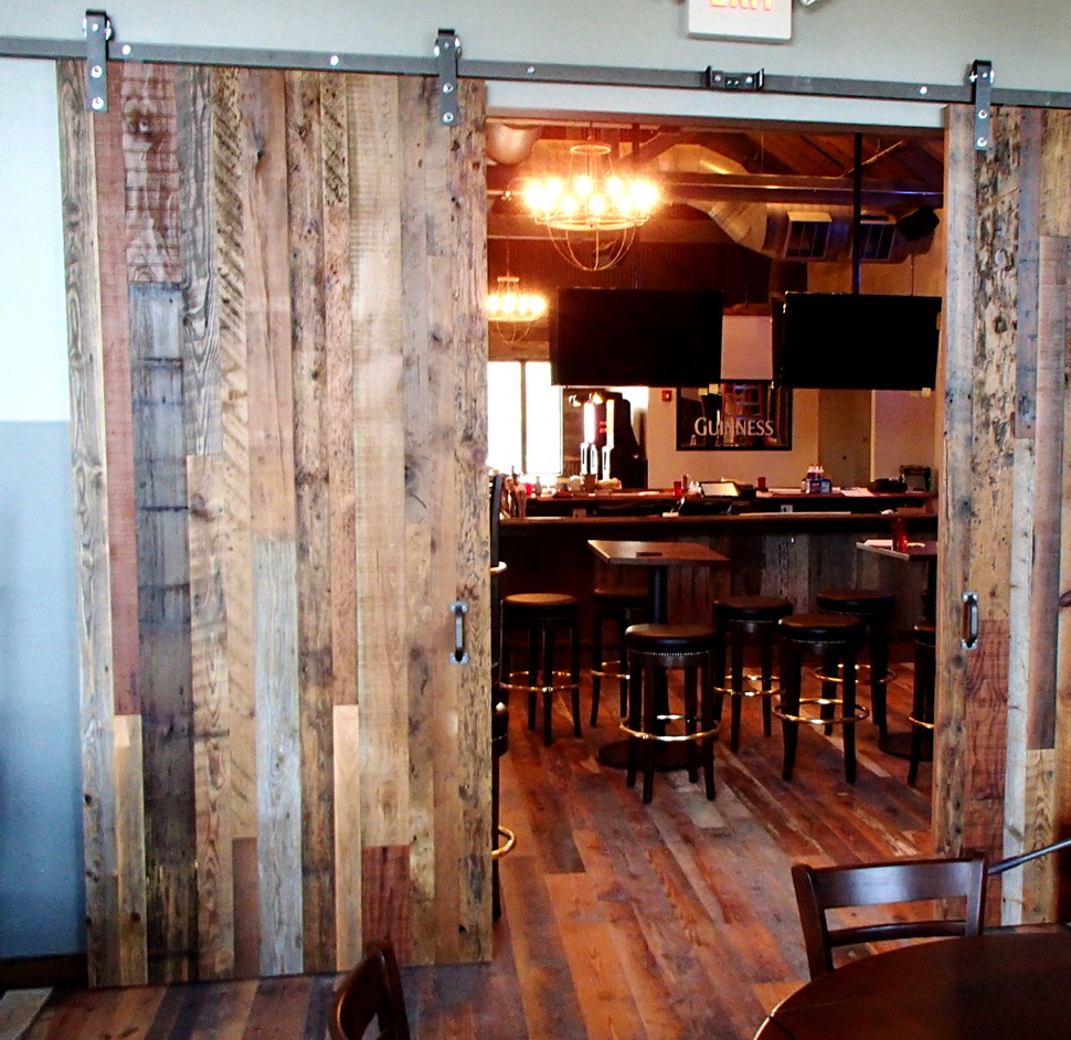 Industrial salvaged mixed woods and silvered hardware give an industrial vibe to these doors. Sliding along a track allows more space for seating and lessens the likelihood of servers or patrons unexpectedly meeting a door swinging open/closed.