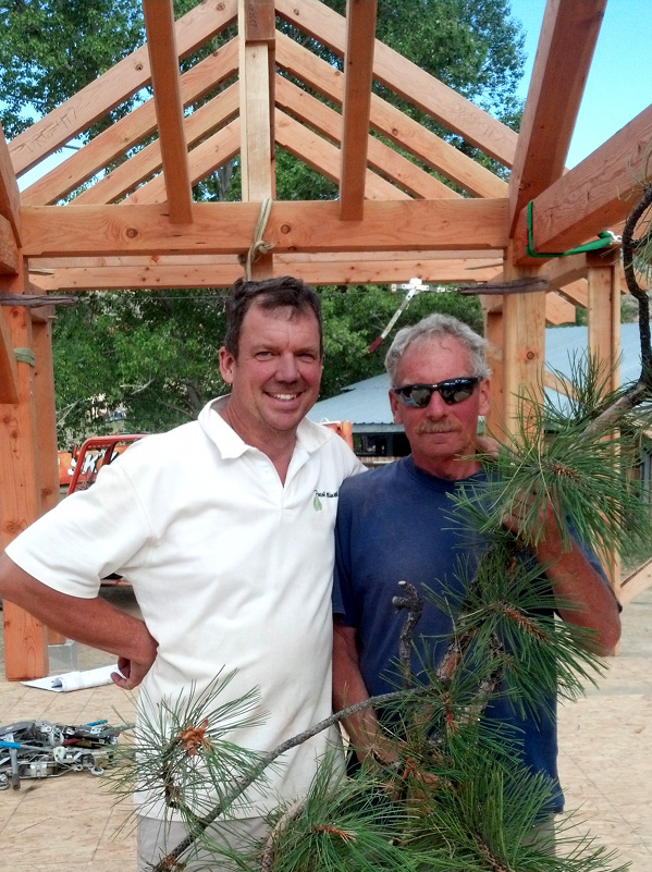 Jonathan and Dave pause for a photo before placing the traditional pine bough at the highest point on the completed frame.