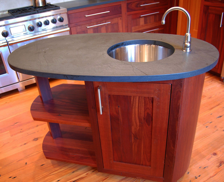A modest Reclaimed Jarrah wood island with a soap stone top and steel sink provides a bit of additional prep space.