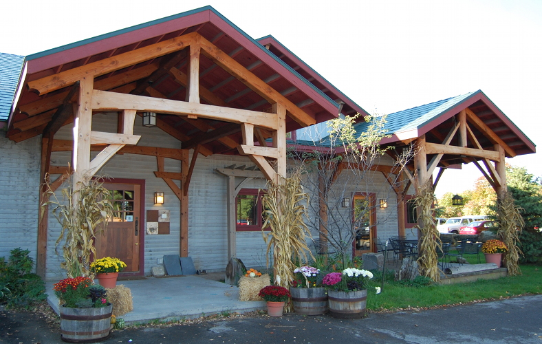 Prior to re-finishing, the timber frame porches of our Farmington headquarters had lost much of their original protective oil finish and natural patina.