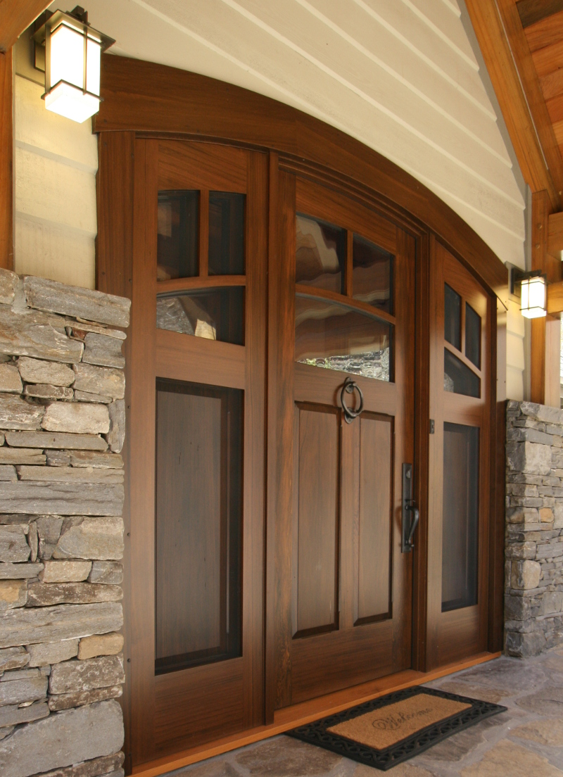 This mountain home's front door (crafted of reclaimed cypress with a custom finish) has 'double' sidelights; the interior set opens to allow airflow through the screened exterior set while ensuring the occasionally adventurous mountain wildlife (bears…) cannot break in.