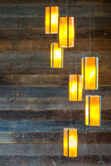 A reclaimed wood paneling wall feature from Pioneer Millworks connects the two levels of the staircase.