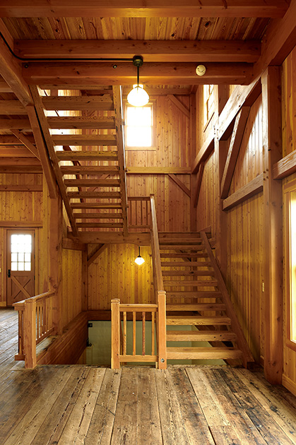 "Within a timber frame party barn ""floating"" stairs connect levels while reminding visitors of open rung ladders common to barn spaces."
