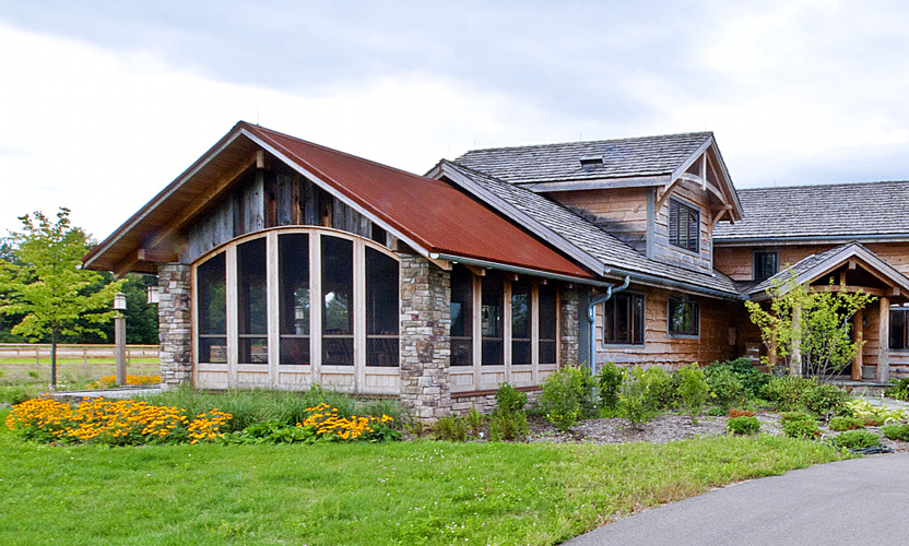 Porches are perfect spaces to combine elements. Reclaimed barn siding, stone, reclaimed timber, custom arched screens, and more. For a family in Mendon, New York, this porch is the place to be, day or night.