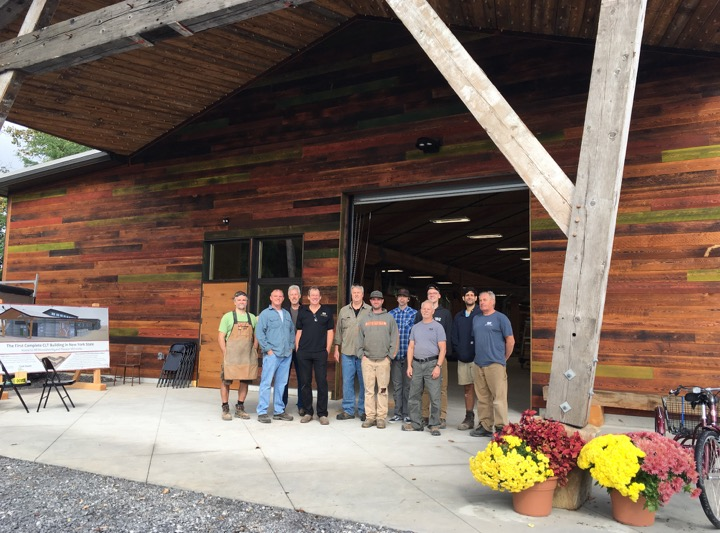The NEWwoodworks team gathered at the entry to their CLT (Cross Laminated Timber) woodworking shop, the first of its kind in New York State.