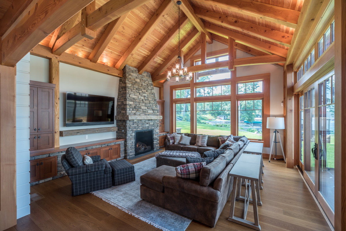 The stone of the fireplace flows down to a lower stone wall (embedded with custom wood cabinets) and continues flowing through the lower level of the home. Photo (c) Scott Hemenway.