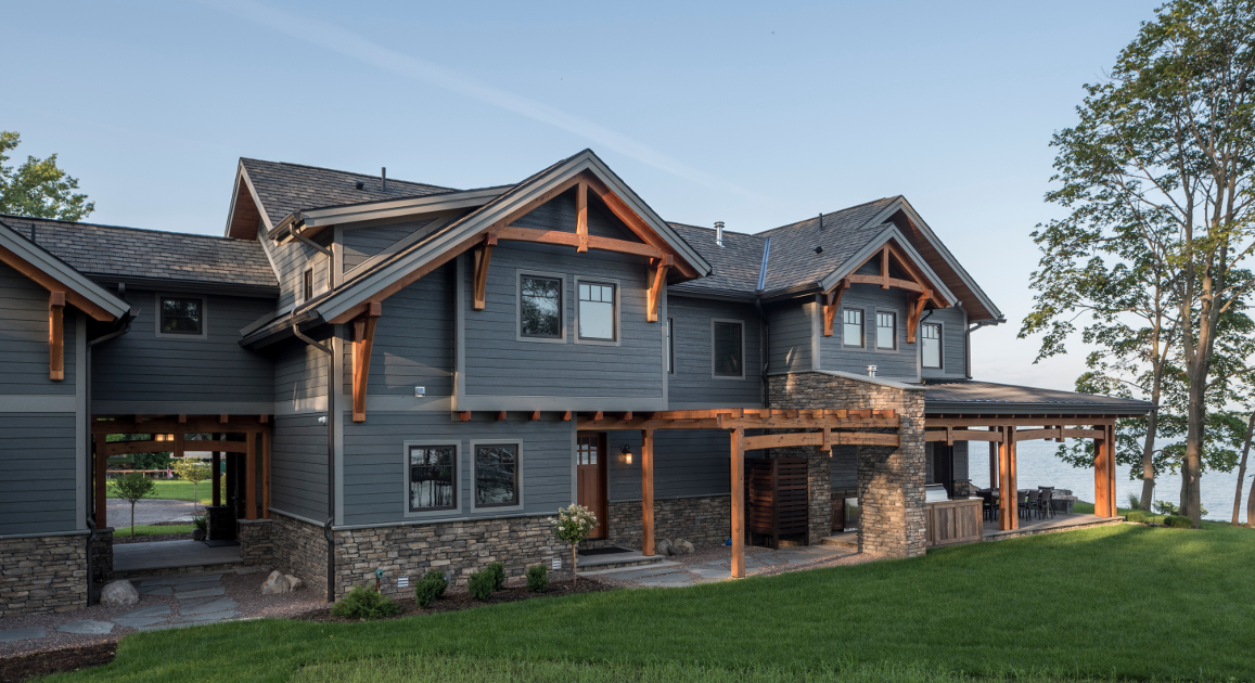 The timber frame breezeway (left) is a favorite feature of the exterior of this project. Sawn curves in the bottom of the paired beams of the breezeway and porch give a consistent craftsman-inspired flow to exterior timber elements.