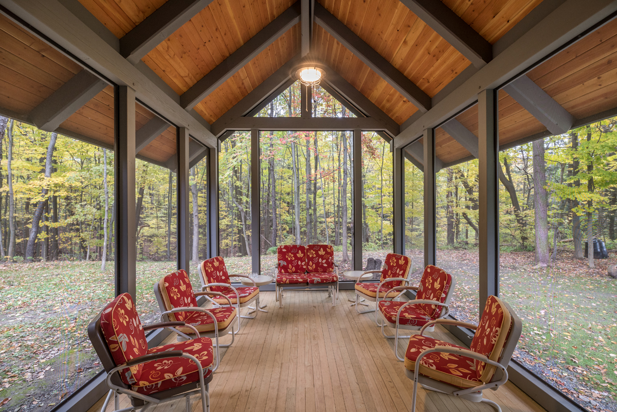 The screen porch extends into the woods, immersed in nature while still providing shelter. Photo (c) Scott Hemenway.