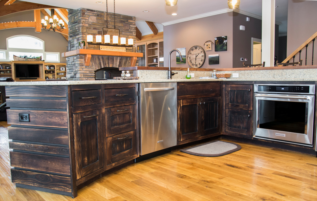 "Broad, open views of the living and dining spaces are enjoyed from the cook's vantage over the island of this lake home kitchen. Reclaimed oak was ""toasted"" to a darker patina adding a bit of rich color to an otherwise light palette."